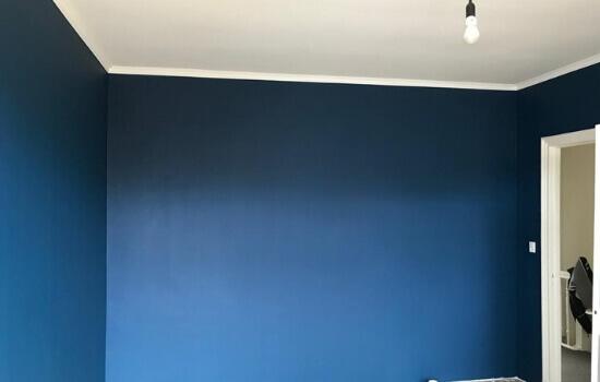 Slaapkamer voorzien van blauwe muur